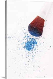 Eyeshadow brush and loose blue eyeshadow powder, close-up