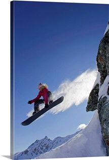 Female snowboarder jumping off a rock