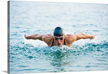 Female swimmer at butterfly stroke in the sea
