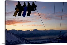 Four snowboarders are silhouetted on a ski lift at sunset.