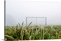 Frost and fog and football goal on soccer field.