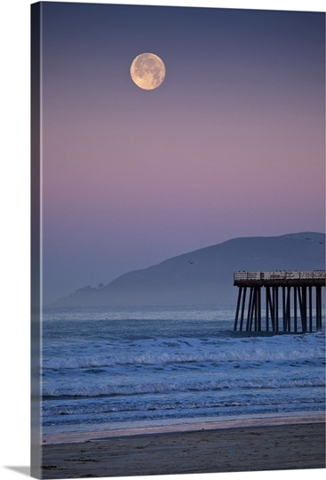 Full moon sets over  Pismo Beach at sunrise on winter morning.