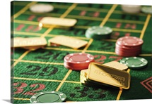 Gambling chips and gold bars on roulette table
