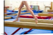 Girl running on balance beam, low section