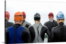 Group of triathletes standing by lake