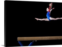 Gymnast leaping on balance beam