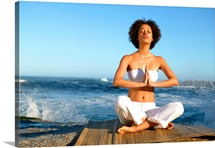 Meditating woman sitting cross legged with back to the sea