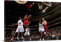 Mike James of the Houston Rockets goes to the basket over Reggie Evans