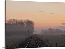 Misty morning sunrise by single railway track with three deer crossing track