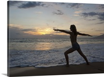 Mixed race woman practicing yoga on beach