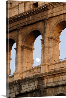 Moon framed by the arches of the Colosseum in Rome, Italy