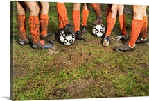 Muddy legs of soccer players