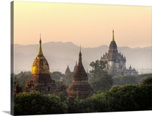 Needle-like spires of ancient Buddhist temples, golden in light of sunset.