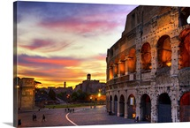 Non-traditional composition of Colosseum back lit with colors of setting sky.