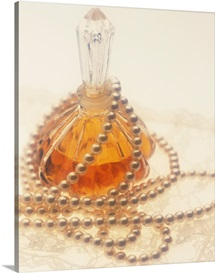 Pearl necklace draped around a perfume bottle