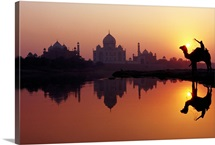 Person sitting on camel in front of Taj Mahal silhouetted