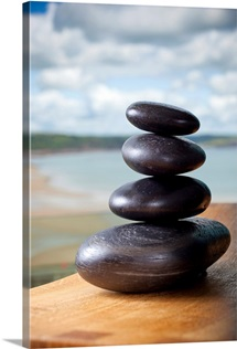 Pile of massage stones on wooden board in front of ocean
