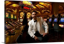Portrait of man sitting at casino slot machine with cigar in mouth, smiling