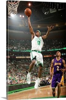 Rajon Rondo of the Boston Celtics lays the ball up over Derek Fisher