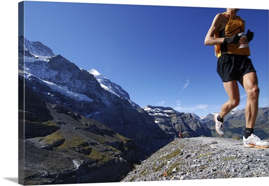 Runner in marathon on moraine below Mount Jungfraun, Switzerland