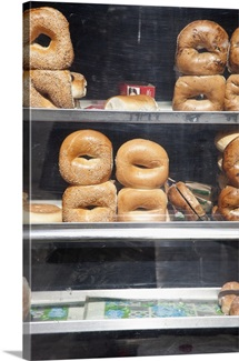 Selection of bagels on shelves behind a shop window
