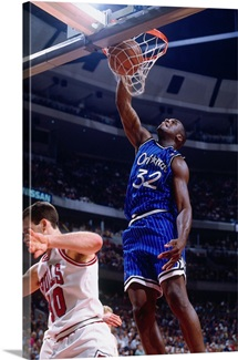 Shaquille O'Neal of the Orlando Magic dunks against Jud Buechler
