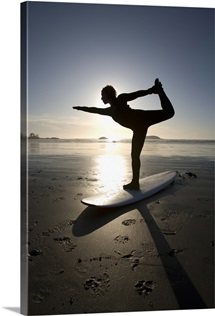 silhouette of female surfer doing bow pulling yoga pose