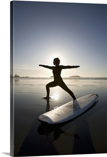 silhouette of female surfer doing warrior yoga pose