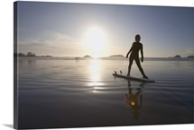 silhouette of female surfer doing yoga stretches