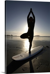 silhouette of female surfer doing yoga tree pose