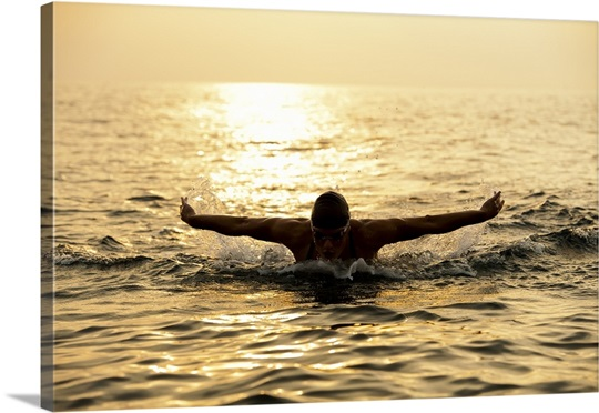 Silhouette of female swimmer at sunset