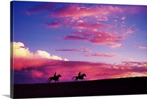 Silhouette of horseback riders at sunset in Colorado
