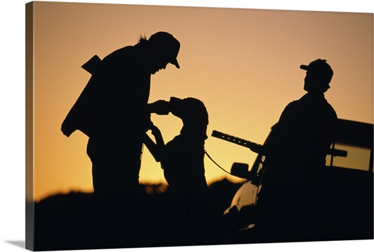 Silhouette of hunters with dog at sunset