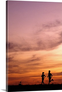 Silhouette of runners at sunset