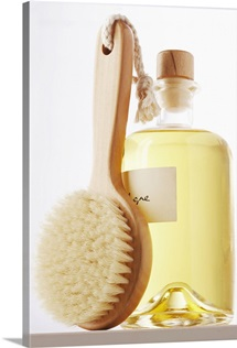 Small bath brush leaning against jar of eau de cologne, close-up