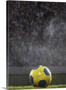 Soccer ball on field in rain