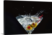 Splashing martini with olives against black background, close-up
