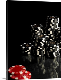 Stacks of black and white gambling chips, red chips in foreground