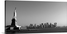 Statue of Liberty looking over Manhattan, black and white skyline, New York City