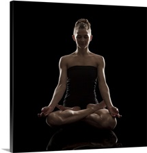 Studio shot of young woman meditating in lotus position, padmasana