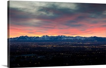 Sun setting over snowy mountains of Wasatch Valley in Salt Lake City, Utah.