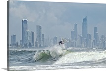 Surfer at burleigh heads with skyline of Surfers Paradise in background.