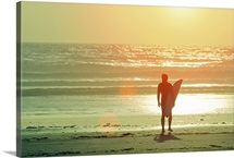 Surfer stands by shore as sun goes down.