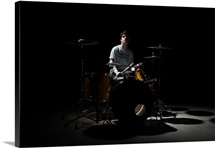 Teenage boy sitting behind drum kit