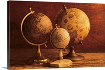 Three globes with world map backdrop
