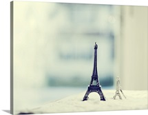 Two Eiffel Tower statues on white antique table with blue and white blurry background.