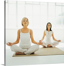 two women sitting on the floor meditating