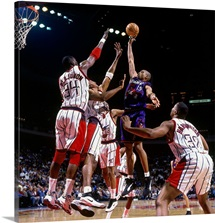 Vince Carter of the Toronto Raptors attempts a layup against Hakeem Olajuwon