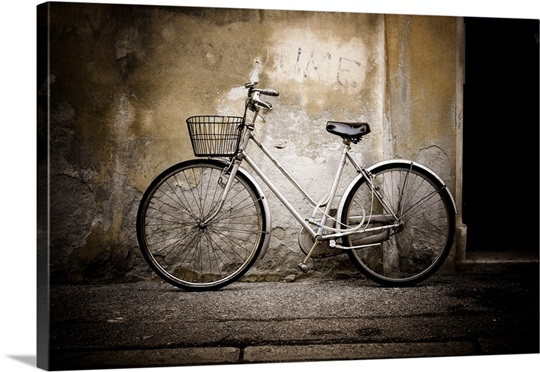 White bicycle leaning against cement wall of building