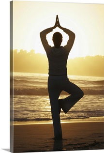 Woman doing yoga on beach at sunrise